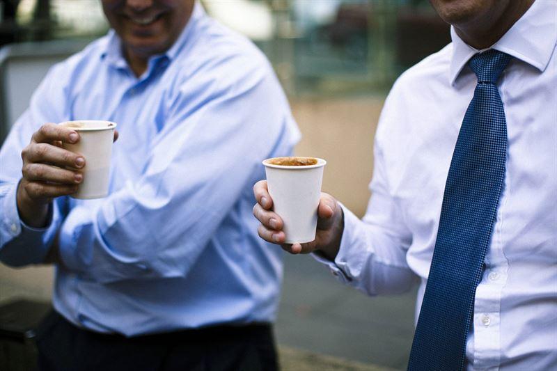 Due uomini bevono caffè in bicchieri di carta