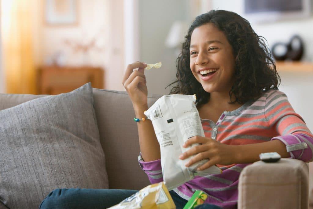 Ragazza mangia le patatine sul divano